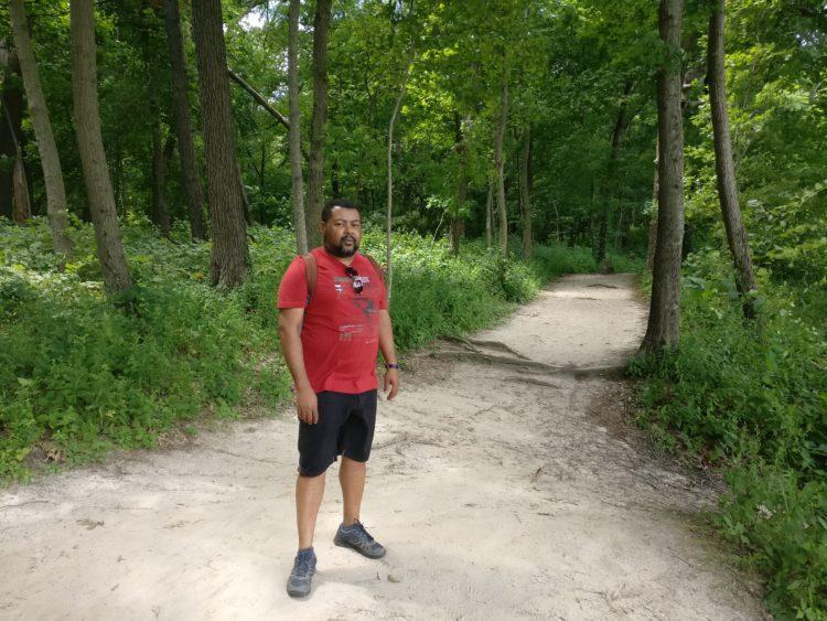 Mann mit Rucksack im Wald beim Wandern
